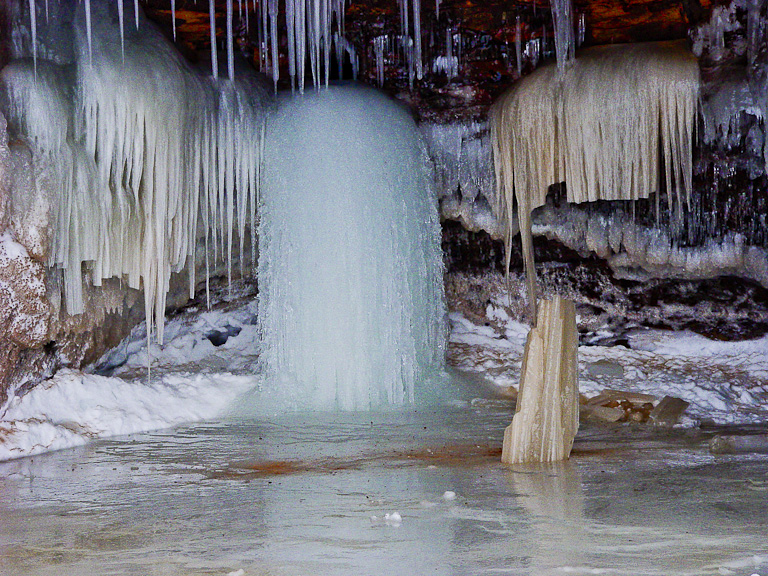 As the water flows through mineral deposits, different colors appear in the ice created by it.